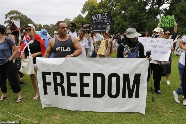'Health cannot be injected' and a 'FREEDOM' sign are seen at the anti-vax march on Saturday