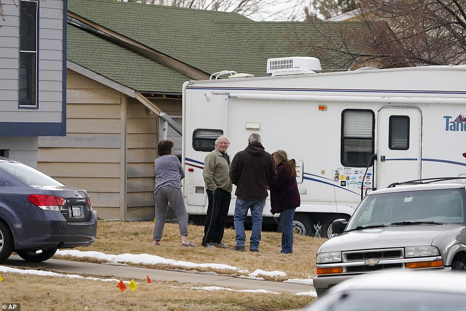 Neighbors gather on the lawn next to the home of Kirby Klements after a piece of debris crushed the man's pickup truck parked next to his home in Broomfield