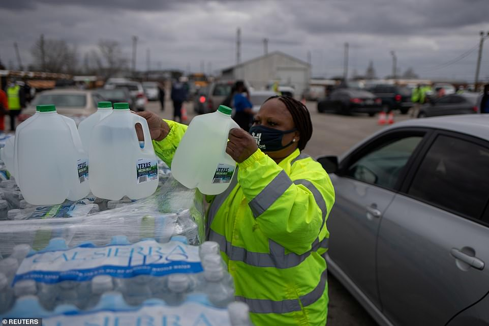 Volunteer Elizabeth Murray helps hand water to local residents at Butler Stadium on Sunday after the city of Houston implemented a boil water advisory following an unprecedented winter storm in Houston