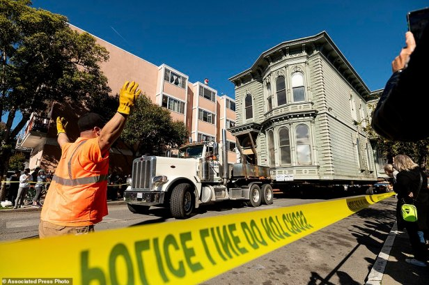 A worker signals to a truck driver pulling a Victorian home through San Francisco on Sunday