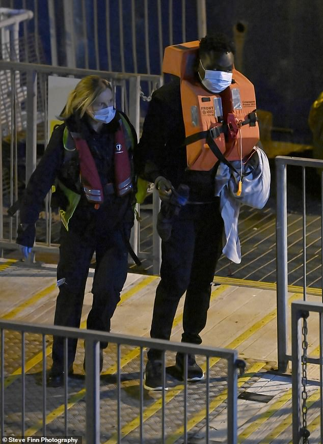 This man was seen wearing a large orange lifejacket as he was escorted to shore by an official