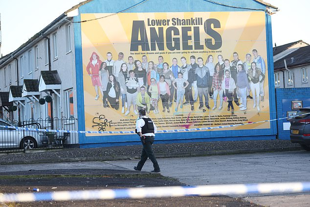A police officer stands at the scene in Belfast after a man was taken to hospital in a critical condition
