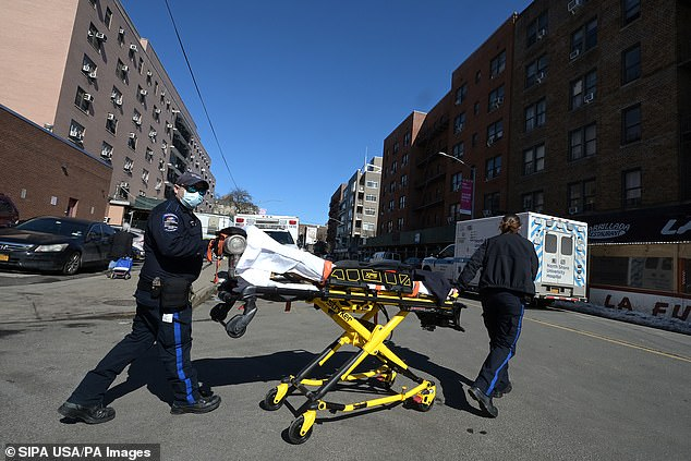 Two EMTs return to their ambulance with a stretcher after dropping off a patient at a Queens hospital on Sunday