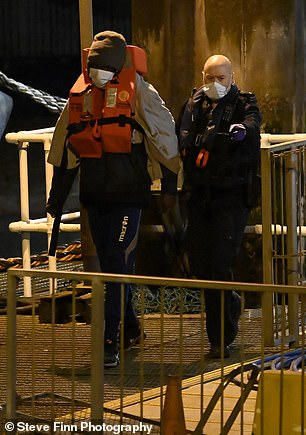 A man wearing a mask, hat and lifejacket is told where to go by a British authority