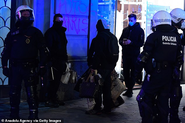 Spanish police collect bags looted from a shop during Sunday's protests. Shops in central Barcelona have had windows smashed and items stolen over several evenings