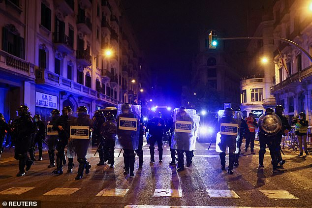 Catalan police were pelted with rocks, bottles, bins and firecrackers for half an hour before they moved in to clear the street in front of the station