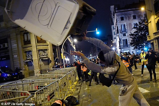 As in previous days, Sunday's rallies began peacefully but descended into violence as night fell, with a crowd of several hundred people marching to the National Police headquarters. Pictured: A bin is thrown at police officers