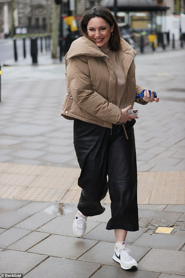 Spring in her step: The model, 41, looked radiant in leather trousers and a tan padded jacket which kept her warm in the capital's wet weather