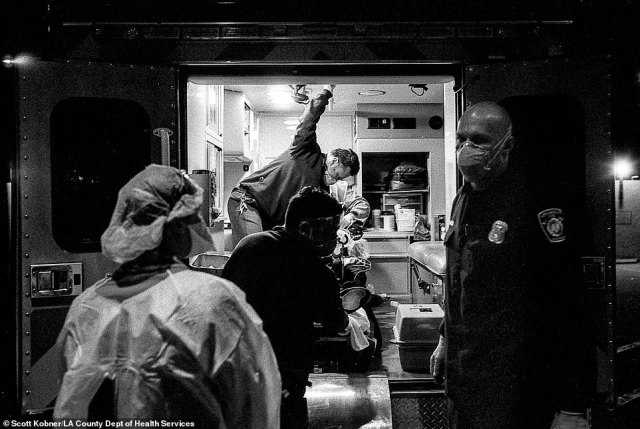 A Los Angeles Fire Department crew, amid a sleepless 24-hour shift, gives a report to a County-USC emergency physician on the ambulance ramp. Inside, the rest of the ER team prepares a bed for the critically ill COVID patient