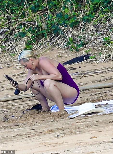 Phone time: Perry made sure she hadn't missed anything while enjoying the sun and sand