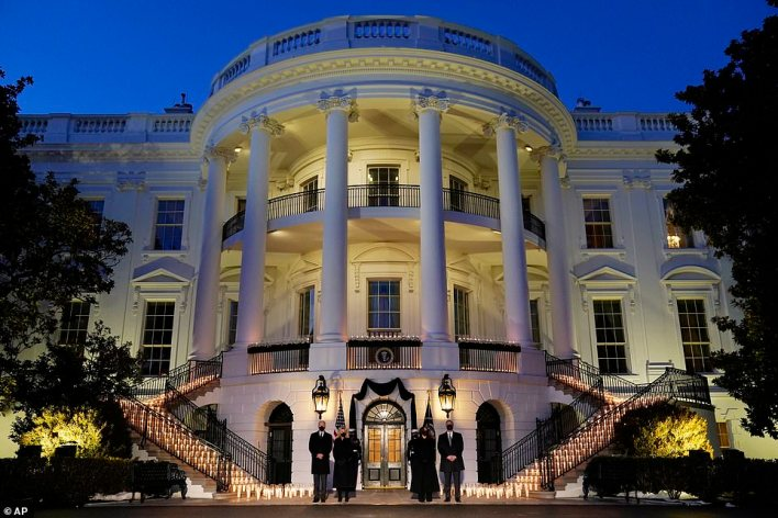 Lit in memory: The South Portico was illuminated by candles for the ceremony of remembrance, and fedeal flags were lowered to half staff for five days of mourning