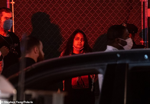 Urooj Rahman stands by the side of the sidewalk after being arrested for throwing a Molotov cocktail at an NYPD van in Brooklyn