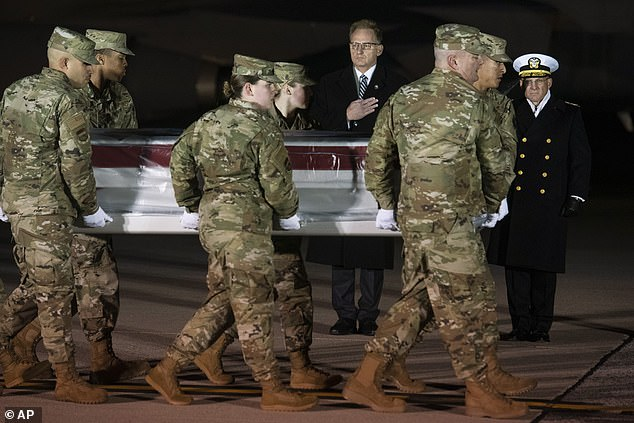 Acting Navy Secretary Thomas Modly, center, and Navy Adm. Michael Gilday, Chief of Naval Operations, right, look on as an Air Force carry team moves the transfer case containing the remains of Navy Seaman Apprentice Cameron Scott Walters