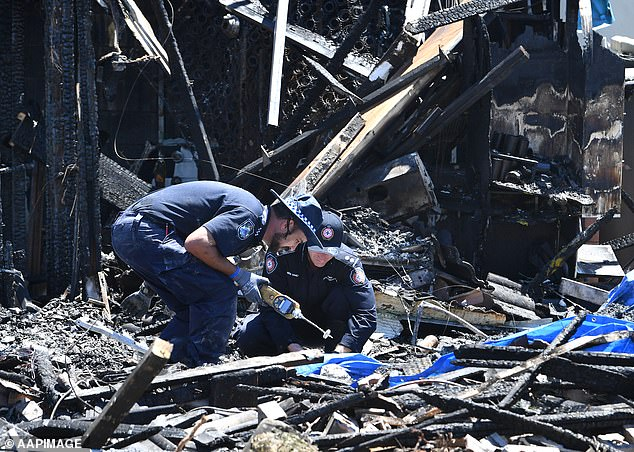 Forensic police are seen sifting through remains of a townhouse that was destroyed by fire at Browns Plains