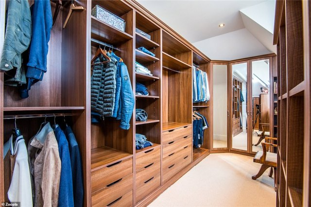 There is a a more traditionally styled dressing room in the Westcliff-On-Sea home, with wooden shelving and full-height mirrors