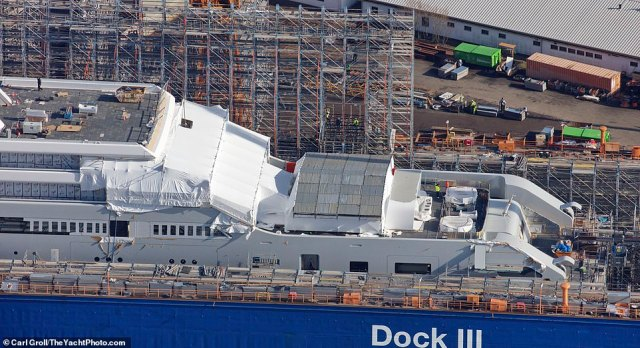 The yacht is covered in tarpaulin and materials as shop builders finish works on the massive boat at the end of December. She is expected to set sail in the summer