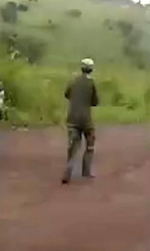 One man wearing camouflage gear clothes is seen running up the road towards where the truck is stopped, as other people move in the opposite direction.