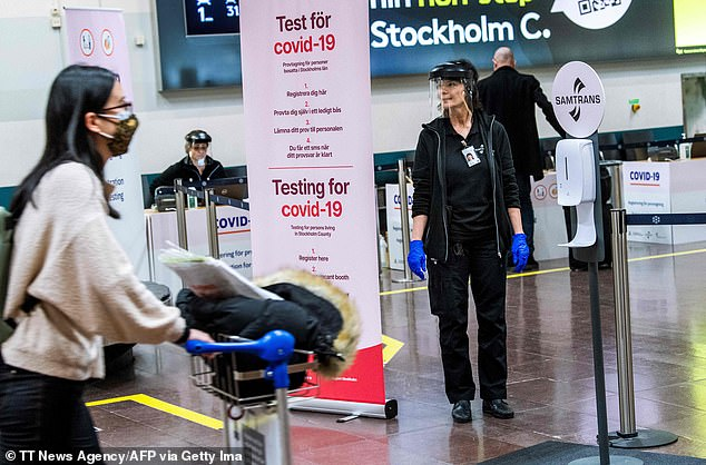 Pictured: A womanworks at the sampling station for the coronavirus (Covid-19) test at Stockholm's Arlanda Airport, for travellers who arrive with international flights on February 22