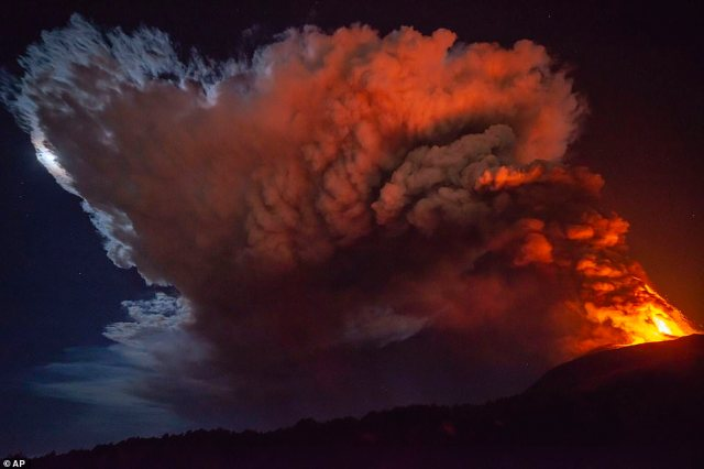 Pictured: A huge plume of smoke and ash rises into the sky from Mount Etna late on Monday night, with the moon being obscured by the cloud.There have been no reports of injuries or fatalities due to the eruption but a nearby airport was forced to close temporarily