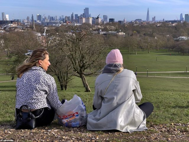 Two women enjoy the sun on Primrose Hill, London, today amid the good weather