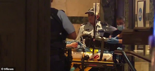 A woman is fighting for life in hospital after she was allegedly assaulted with a hammer in a hotel room on Tuesday night. She's pictured on a stretcher being treated by paramedics