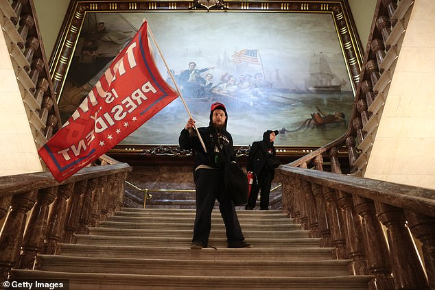 A protester holds a Trump flag inside the US Capitol Building near the Senate Chamber on January 06, 2021 in Washington, DC