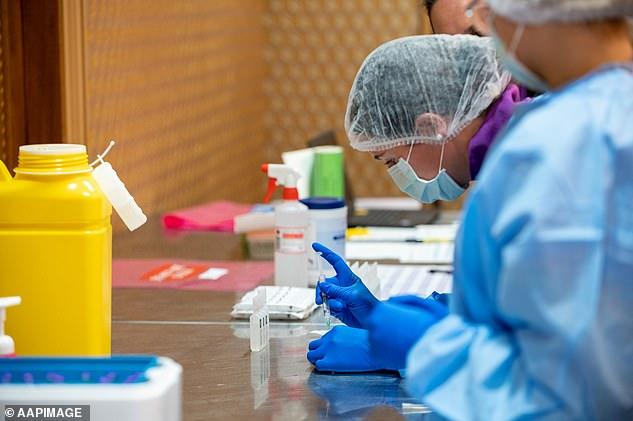 Medical workers prepare the Pfizer coronavirus vaccine at the Hyatt quarantine hotel in Perth on Monday