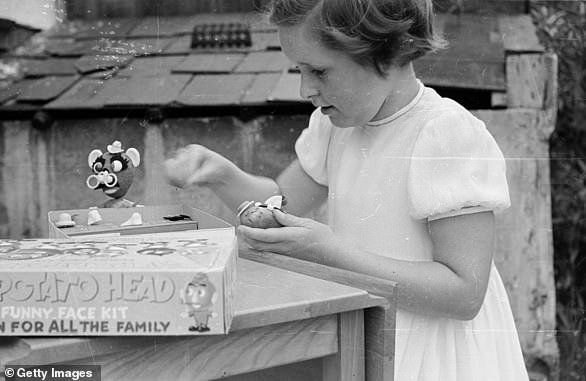 A boy playing with Mr Potato Head in 1953. Mr Potato Head first hit shelves in 1952 as a kit of plastic parts and accessories for children to stick to a real potato.