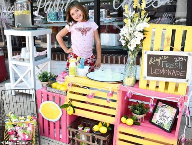 Liza Scott, 7, has been selling lemonade at her mom's bakery to pay for her own brain surgeries after she was diagnosed with multiple cerebral malformations. Pictured Liza at her lemonade stand