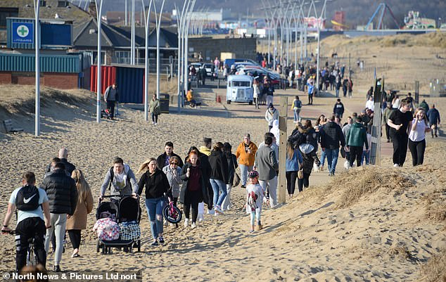 Crowds of people walk close together along South Shields beach, in South Tyneside, this afternoon
