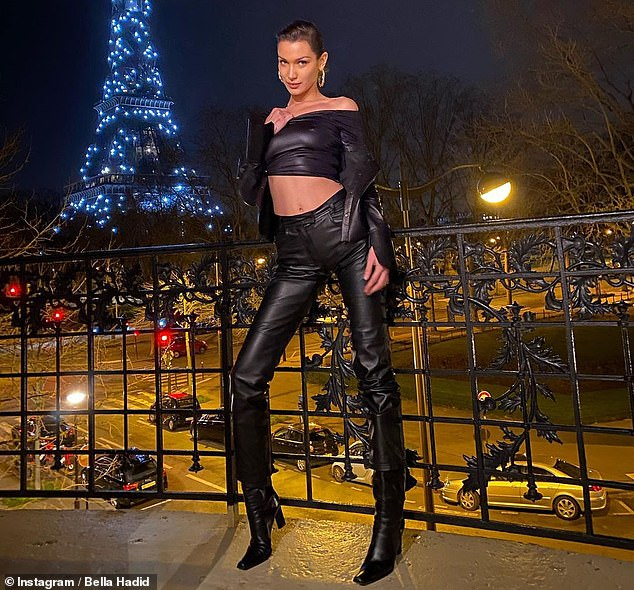 Sizzling: The model posed in an avant-garde leather crop top and matching flared pants for a trio of snaps in front of the illuminated Eiffel Tower