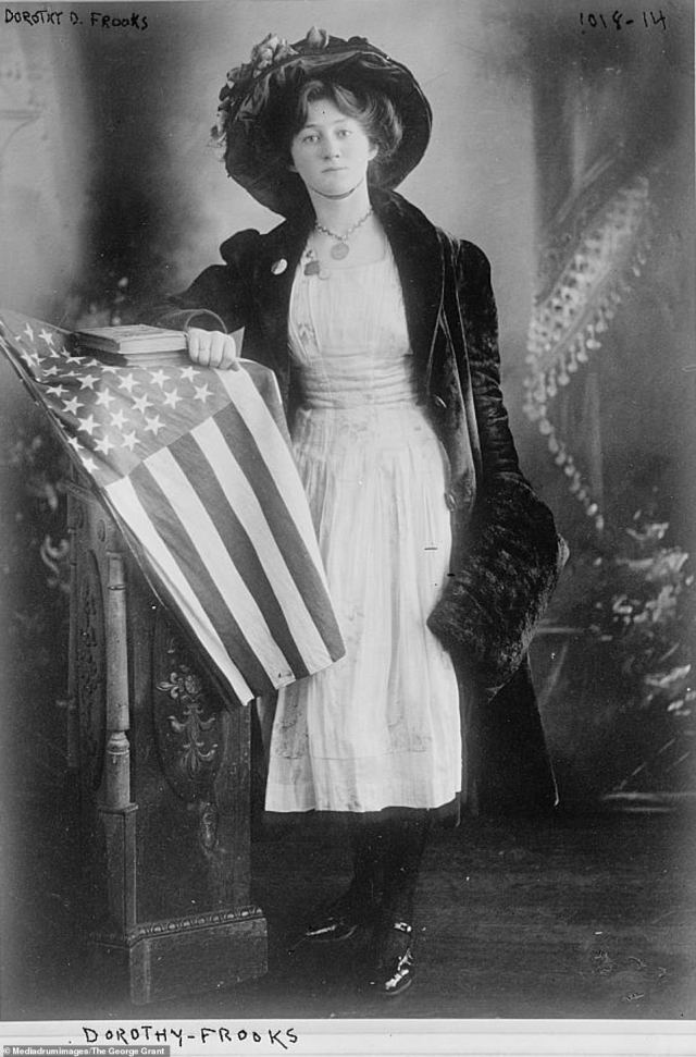 Dorothy D Frooks, pictured, was anauthor, publisher, military officer, lawyer, and suffragette. She found her voice at an early age after being employed by her mother's London society friends to give street-corner speeches. In this picture, Frooks is seen leaning on a wooden pillar, upon which an American flag is draped. During the First World War, Frooks served as chief yeoman in the United States Navy. By the 1920s, Frooks was working as the Salvation Army's first full-time lawyer