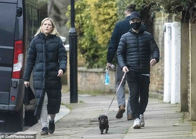 Make way: Dec looked relaxed in a quilted jacket and jogging pants as he guided the curious dog along a narrow path