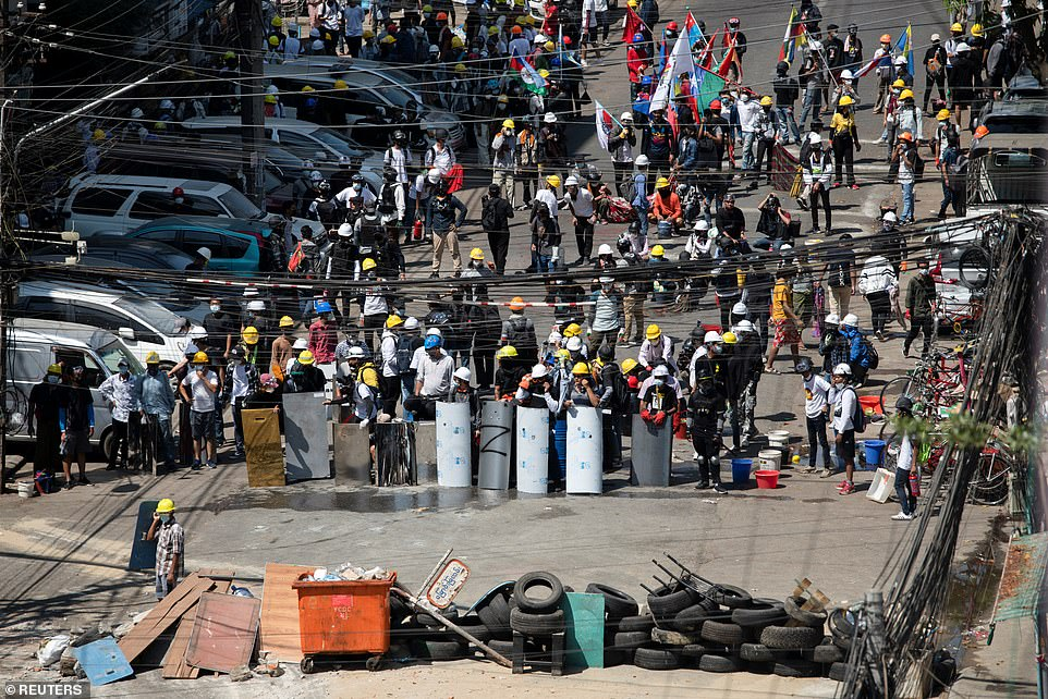 Demonstrators block a road with tyres, bins and pieces of wood during an anti-coup protest in Yangon whilst they hold makeshift shields on March 4