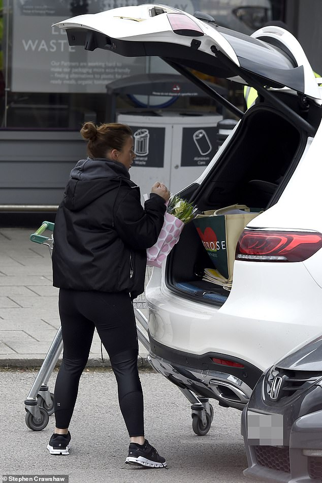 Casual: The mother of four wore a pink t-shirt and a gray hooded jacket, layered over a black windbreaker style jacket