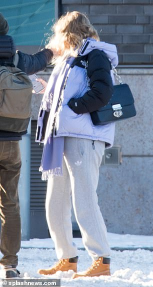 Out and about: She accessorised with a purple scarf and carried her belongings in a black handbag, while covering her face with a coronavirus mask