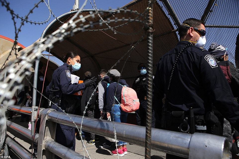 It comes after Biden's rolled back Trump policies such as the Migrant Protection Protocol. Pictured, U.S.police supervise the access of migrants to the U.S. as part of the Migrant Protection Protocol (MPP) program at the border with Mexico