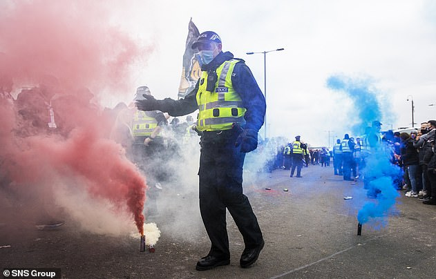 A strong police presence was at the scene, as one officer walks between red and blue flares