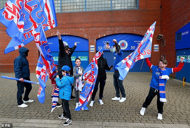 Fans gather with flags to celebrate at Ibrox as the news filters through of Celtic's draw