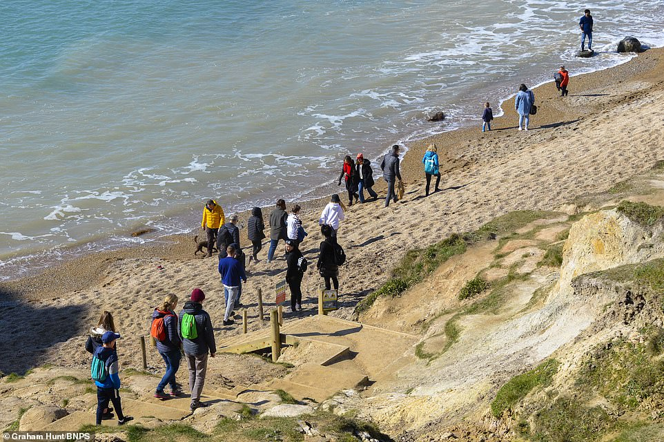 Crowds flocked to outdoor spaces across the UK to enjoy the outbreaks of sunshine amid warnings that temperatures will plummet below freezing this evening. Pictured:Visitors enjoying the sunshine as they walk on the beach at Durdle Door at Lulworth in Dorset
