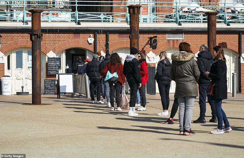 It comes as Britain prepares for its first step toward normality with lockdown restrictions easing from tomorrow. Pictured: Queuing for coffee on the seafront as the warm weather brings people to the beach in Brighton earlier today