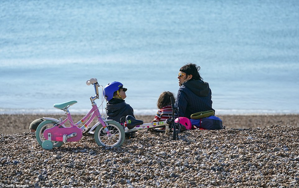 Meanwhile, all pupils and students will return to schools and colleges across England. Pictured: Woman sits on the beach with two children and their brightly coloured bicycles