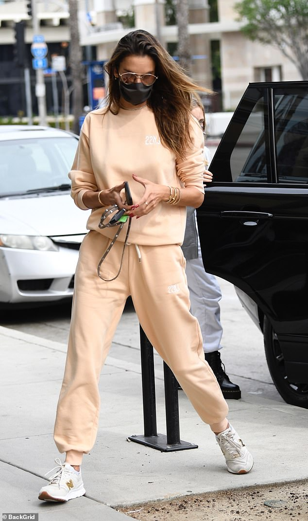 Cool laid back: The former model was seen stepping out of her SUV with her 12-year-old daughter Anja right behind her and her eight-year-old son Noah in a peach-colored tracksuit and sneakers.