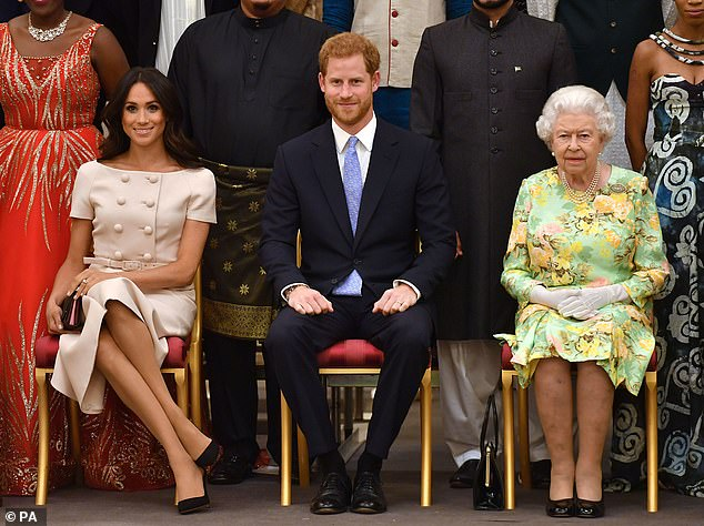 The Queen sits with the Duke and Duchess of Sussex at Buckingham Palce on June 26, 2018