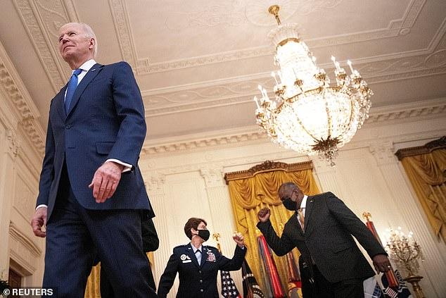 U.S. Air Force General Jacqueline Van Ovost fist bumps Defense Secretary Lloyd J. Austin following President Joe Biden's remarks on International Women's Day