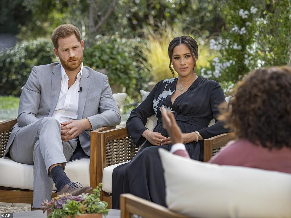 The Queen, Prince Charles and Prince William were all locked in crisis talks over how to react to a string of incendiary accusations unleashed by Harry and wife Meghan during a two-hour special with Oprah Winfrey on American TV (pictured)