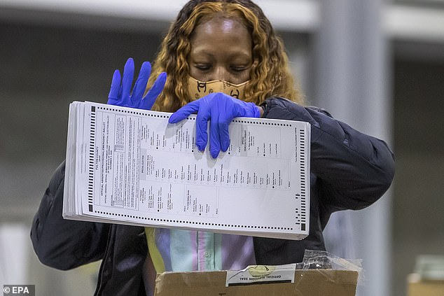 Officials with the Fulton County Registration and Elections Department conduct a machine recount of the county's presidential election ballots at the the Georgia World Congress Center in Atlanta, Georgia, USA, 30 November 2020. A statewide recount was requested by the campaign of President Donald J. Trump