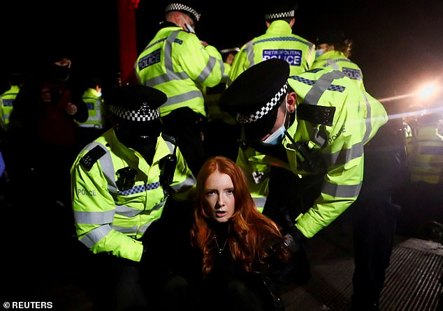 Met Police officers shoved women, pinned protestors to the ground and 'elbowed people in their faces' at a vigil to mourn the death of Sarah Everard, onlookers claim. Pictured:Stark images showed demonstrator Patsy Stevenson being held on the floor by police last night