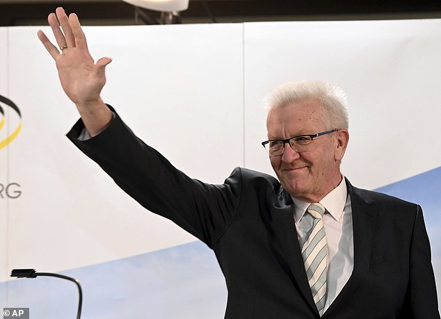 Winfried Kretschmann, Minister President of Baden-Wuerttemberg and top candidate of the Green Party, waves after the announcement of the first results of the state elections in Baden-Wuerttemberg in Stuttgart on Sunday. Exit polls are pointing to defeats for Chancellor Angela Merkel's center-right party CDU in two German state elections