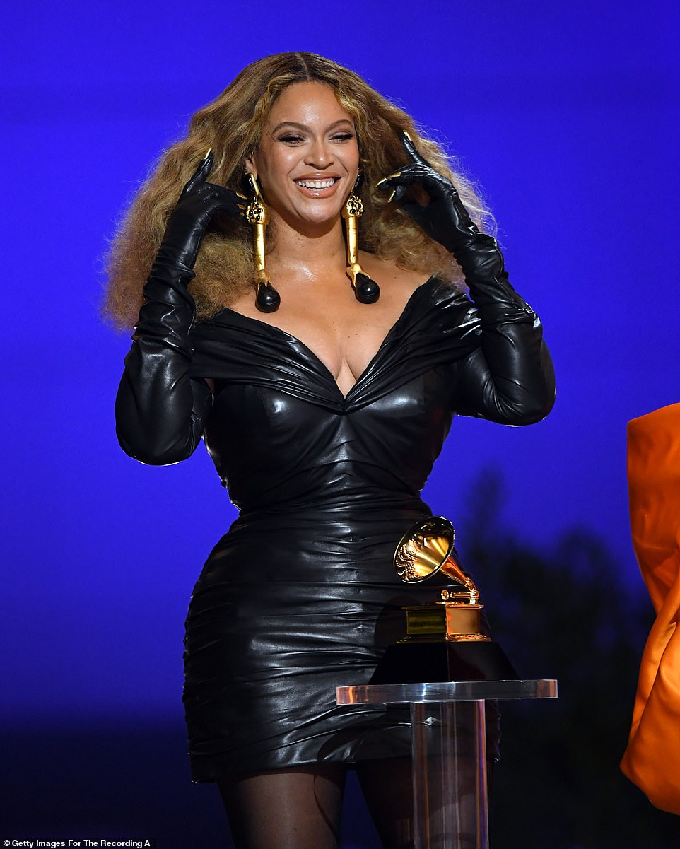 Iconic: Beyonce didn't make it to the red carpet but appeared on stage in a striking black leather look and statement earrings